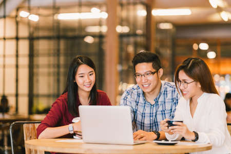 Foto de Young Asian college students group or coworkers using laptop computer together at cafe or university. Casual business, freelance work, coffee break meeting, e-learning or e-commerce activity concept - Imagen libre de derechos
