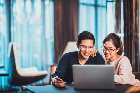 Foto de Young Asian married couple working together using laptop at home or modern office with copy space. Startup family business, SME entrepreneur, business partner, love relationship, or freelance concept - Imagen libre de derechos