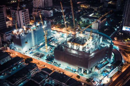 Bangkok, Thailand - Mar 5, 2018: Construction site of shopping center or community mall project in Bangkok, Thailand. Night scene, top view, with light trails of traffic in the city