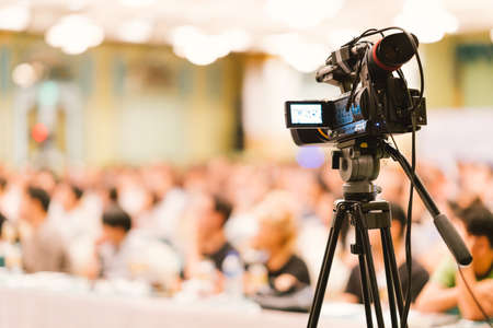 Foto de Video camera set record audience in conference hall seminar event. Company meeting, exhibition convention center, corporate announcement, public speaker, journalism industry, or news reporter concept - Imagen libre de derechos
