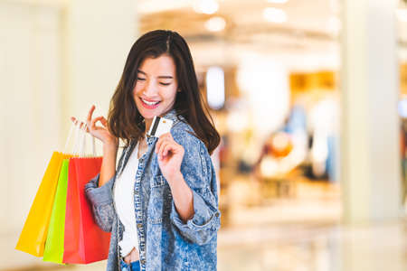 Photo pour Happy beautiful Asian woman smile at credit card, hold shopping bags, copy space on shopping mall background. Shopaholic people, retail special offer price, holiday vacation activity lifestyle concept - image libre de droit