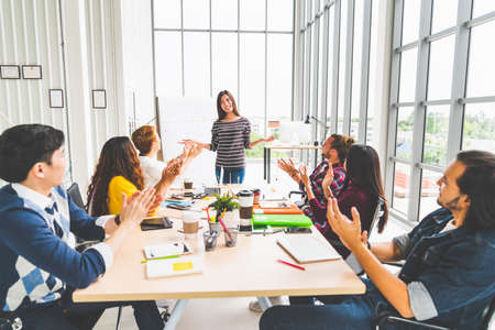 Foto de Multiethnic diverse group of creative team or business coworker clapping hands in project presentation meeting leading by Asian woman. Success teamwork, modern office work, or startup company concept - Imagen libre de derechos