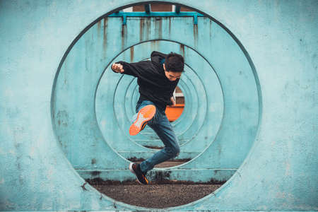 Young Asian active man in action of jumping and kicking, circle looping wall background. Extreme sport activity, parkour outdoor free running, or healthy lifestyle concept