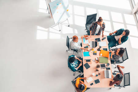 Foto de Multiethnic diverse group of business coworkers in team meeting discussion, top view modern office with copy space. Partnership professional teamwork, startup company, or project brainstorm concept - Imagen libre de derechos