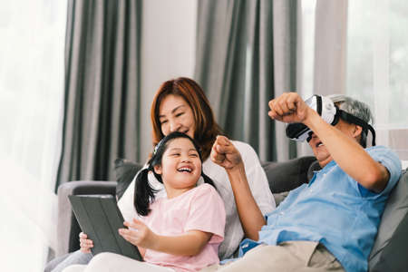 Photo pour Lovely happy people playing Virtual Reality game together, young kid girl using digital tablet, grandfather wearing VR headset. Family life love relationship, or home fun leisure activity concept - image libre de droit