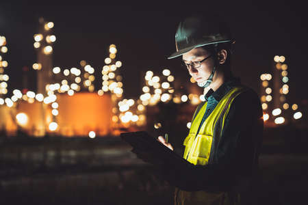 Photo pour Asian man engineer using digital tablet working late night shift at petroleum oil refinery in industrial estate. Chemical engineering, fuel and power generation, petrochemical factory industry concept - image libre de droit