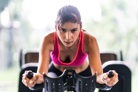 Photo for Beautiful Asian woman exercising on stationary cycling machine in indoor fitness gym, determination face. Sport recreational activity, people workout, or healthy lifestyle concept - Royalty Free Image