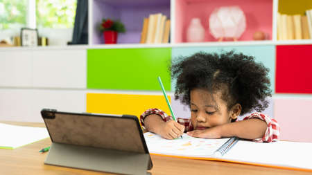 Photo pour Young African American kid girl studying using digital tablet, preschool child study at home school. Children education, self isolation, coronavirus outbreak social distancing or homeschooling concept - image libre de droit