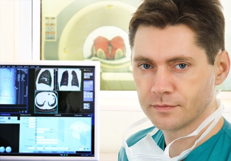 Male doctor and computer tomographic scanner in hospital
