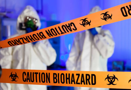 Two scientists behind caution tape in hazardous biochemicals laboratory