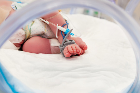 Pulse Oximeter Sensor and Drip Line on the Foot of Newborn Baby at Children's Hospital