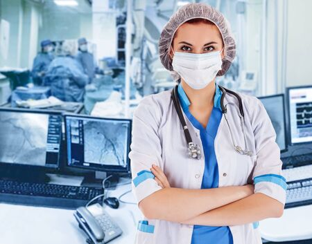Photo pour Female surgeon doctor at operation. Interventional cardiology. . Visualization on the monitor in the operating x-ray lab on background - image libre de droit