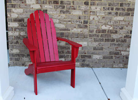 A wooden red chair on a front porch by a brick wallの写真素材