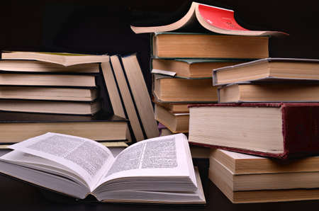 open book and pile of books against a dark background