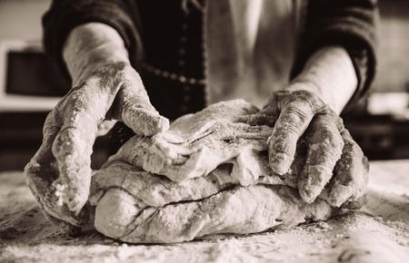 Photo pour old italian grandma making pasta in the kitchen sepia effect - image libre de droit
