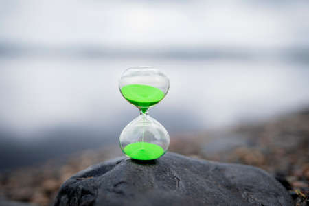Photo pour Modern Hourglass with green background -- sand trickling through the bulbs of a crystal sand glass. every second counts. symbol of time. countdown. - image libre de droit