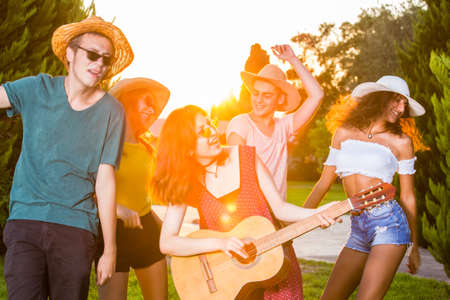 Photo for Group of happy young friends singing and dancing, enjoying summer in park. Front half-length portrait of a girl playing guitar, dancing and smiling. - Royalty Free Image