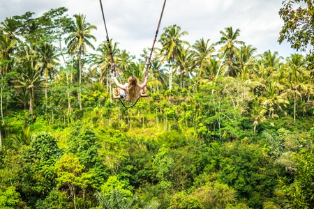 Young tourist woman swinging on the cliff in the jungle rainforest of a tropical Bali island. Indonesian swing.