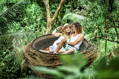 Photo pour Traveler honeymoon couple in decorative nest the jungle of Bali island, Indonesia. Couple in the rainforest. - image libre de droit