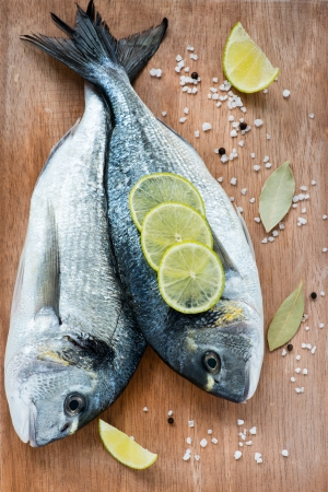 Fresh dorada fish with sea salt, lime and bay leaf over wooden background