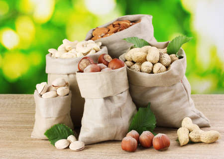 many nuts in bags on green background