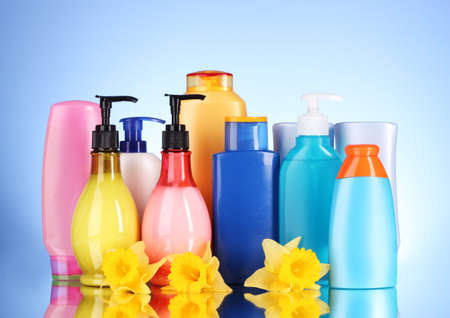 bottles of health and beauty products on blue background with reflection
