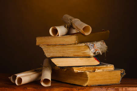 Pile of old books and scroll on brown