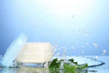 Opened jar of cream in water splash on blue background