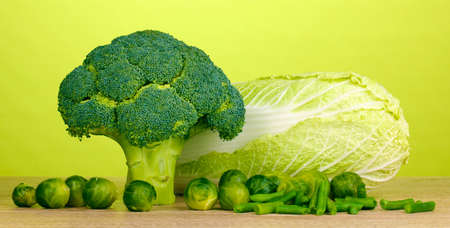 Fresh broccoli and cabbages on wooden table on green background