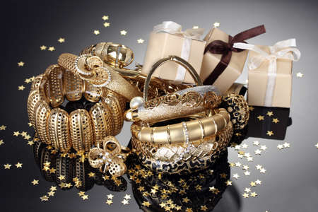 Photo pour Beautiful golden jewelry and gifts on grey background - image libre de droit