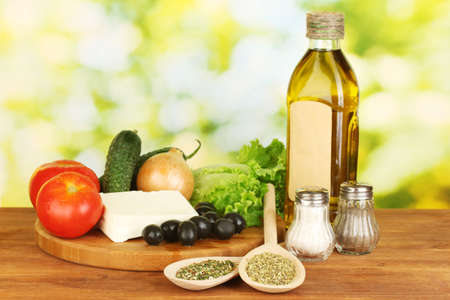 Ingredients for a Greek salad on green background close-up