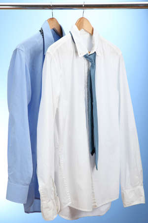 blue and white shirts with tie on wooden hanger on blue background