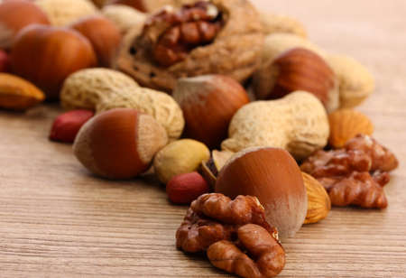 assortment of tasty nuts on wooden background