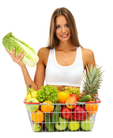 beautiful young woman with fruits and vegetables in shopping basket, isolated on whiteの写真素材