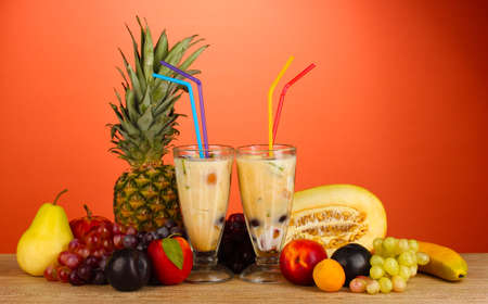 Milk shakes with fruit on red background close-up