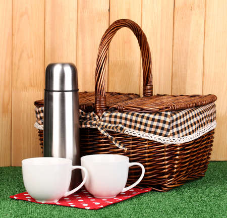 metal thermos with cups and basket on grass on wooden background