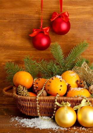 christmas composition in basket with oranges and fir tree, on wooden background