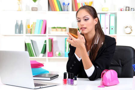 young business woman looking in the mirror and using lipstick at her worlplace