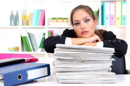 Sad business woman with documents in her workplace