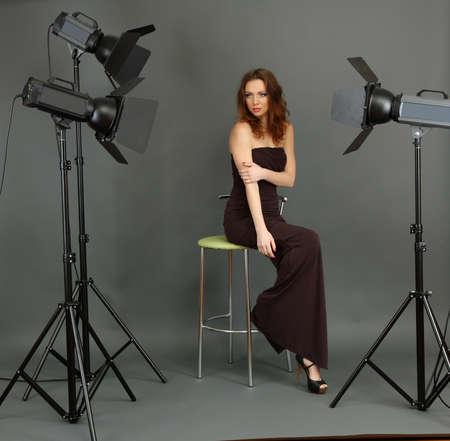 beautiful professional female model resting between shots in photography studio shoot set-up