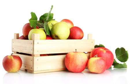 juicy apples with green leaves in wooden crate, isolated on whiteの写真素材
