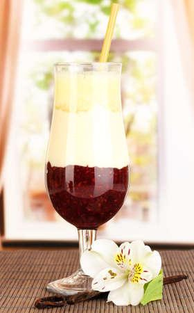 Delicious fruit smoothie on window background