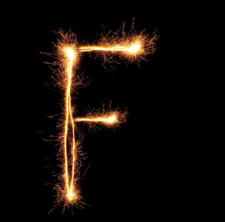 Letter F sparklers on black background