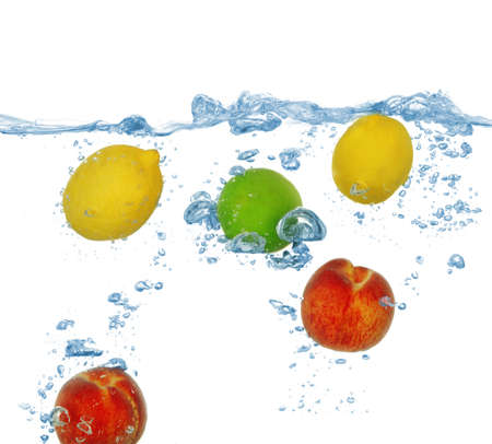 Tropical fruits falling into water with splash isolated on whiteの写真素材