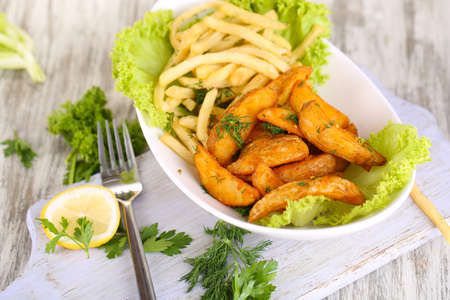 French fries and home potatoes on plate on board on wooden table