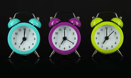 Colorful alarm clock on dark grey background