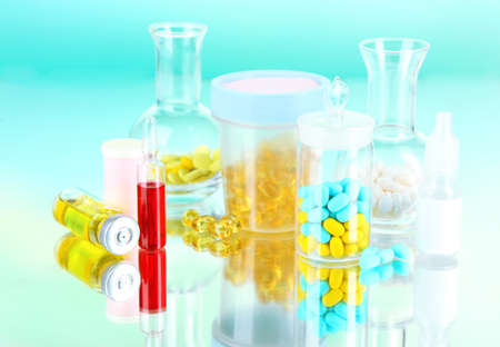 Medical bottles and pills on green background