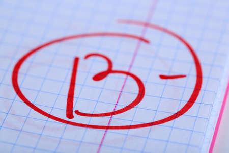 Grade B- written on an exam paper