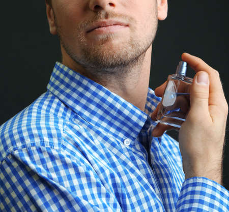 Handsome young man using perfume on black background