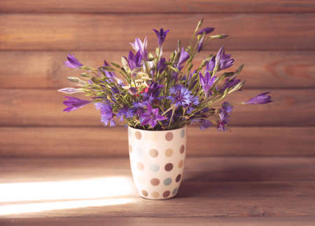 Beautiful wild flowers in vase on wooden background